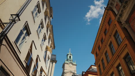 St-Nicholas-(Storkyrkan)-Bell-Tower-In-Stockholm-View-Through-A-Narrow-Street-With-Old-Houses-4k-Vid