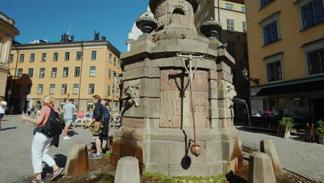 Fountain-With-Drinking-Water-In-The-Old-City-Of-Stockholm-Nearby-Tourists-Walk-A-Popular-Holiday-Des
