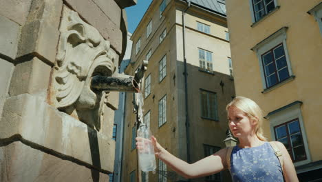 A-Woman-Picks-Up-Water-In-A-Bottle-From-A-Fountain-In-The-Central-Square-Of-Stockholm-Clean-Drinking