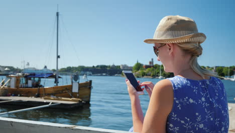 A-Resting-Woman-With-A-Smartphone-Sits-On-The-Embankment-Against-The-Backdrop-Of-The-Sea-And-Moored-