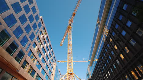 A-Large-Tower-Crane-In-The-Downtown-Of-The-Modern-City-Glass-Office-Buildings-Around-Steadicam-Shot