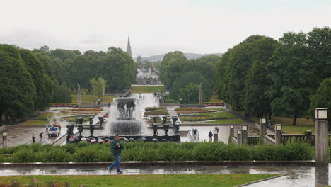 Sculpture-Park-Gustav-Vigeland-Rainy-Weather-A-Lot-Of-Tourists-Walk-Under-The-Umbrellas-In-The-Park