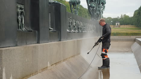 The-Worker-Cleans-The-Fountain-In-The-Sculpture-Park-Of-Gustav-Vigeland