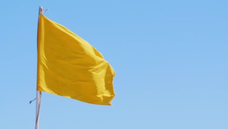 Yellow-Flag-Against-The-Blue-Sky