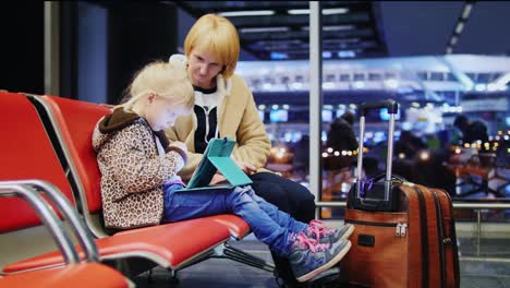 Mother-And-Daughter-Waiting-For-Your-Flight-Little-Girl-Playing-On-A-Tablet