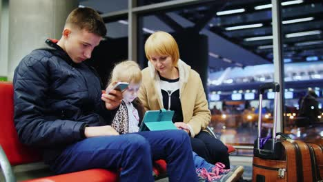 A-Family-Waiting-For-Their-Flight-At-The-Airport-Terminal-Sitting-In-The-Waiting-Room-Using-Gadgets