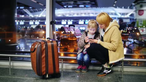 Mom-And-Daughter-Against-The-Window-In-The-Airport