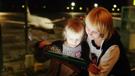 Mom-And-Daughter-Play-On-The-Tablet-At-The-Airport-Late-Evening-The-Airliner-Is-Visible-Outside-The-