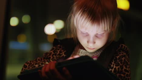 A-Girl-Enjoys-The-Tablet-On-The-Background-Of-A-Large-Window-With-Reflections