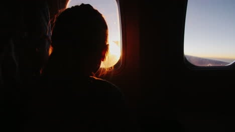 Girl-Sitting-In-An-Airplane-Looking-Out-The-Window-At-The-Rising-Sun