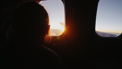 Little-Girl-Sitting-On-The-Plane-With-Delight-Looks-Out-The-Window-At-The-Rising-Sun