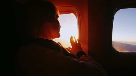 Young-Woman-Looking-At-The-Sun-From-The-Window-Of-An-Airliner