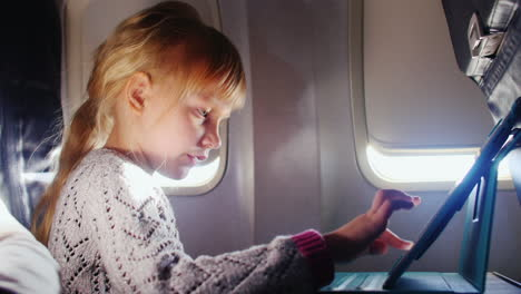 A-Girl-Enjoys-The-Tablet-In-The-Aircraft