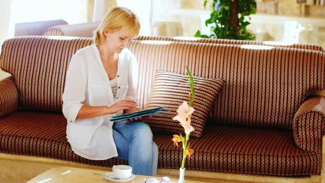 Woman-In-A-Summer-Shirt-Uses-A-Tablet-In-The-Hotel-Lobby