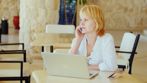 Business-Woman-On-Vacation-Sits-By-The-Laptop-Talking-On-The-Phone-In-Light-Summer-Clothes