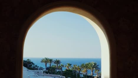 The-Window-Overlooking-The-Sea-And-The-Beach-With-Palm-Trees