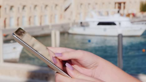 Hands-With-The-Tablet-On-The-Background-Of-Yachts