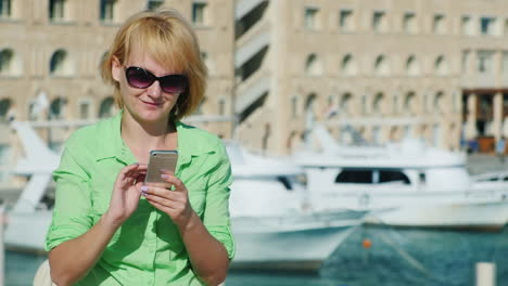 Woman-Typing-Sms-On-A-Tourist-City-Skyline-With-Yachts