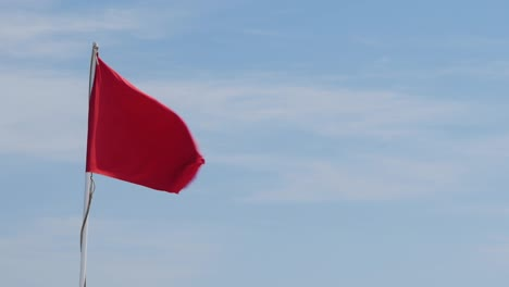 Red-Flag-On-A-Background-Of-Blue-Sky