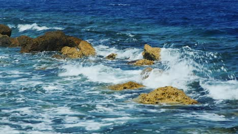 Waves-Breaking-On-Rocks-On-A-Sunny-Day