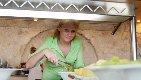Woman-Puts-Vegetables-In-The-Dishes-In-The-Cafe-With-Self-Service