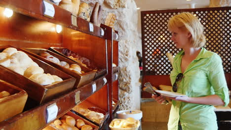 Attractive-Woman-Chooses-Bread-At-The-Cafe-With-Self-Service
