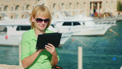 A-Female-Tourist-Enjoys-The-Tablet-Against-The-Backdrop-Of-The-Bay-With-Yachts