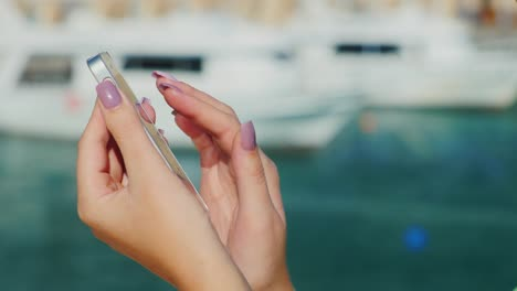 Female-Hands-With-Telephone-On-A-Background-Of-A-Blurry-Plan-With-The-Sea-And-Yachts-Always-Connecte