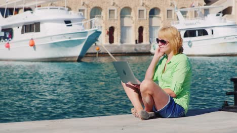 Girl-Tourist-Uses-A-Laptop-On-The-Background-Of-The-Urban-Landscape-With-Yachts
