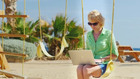 Woman-Sitting-On-A-Swing-And-Uses-A-Laptop