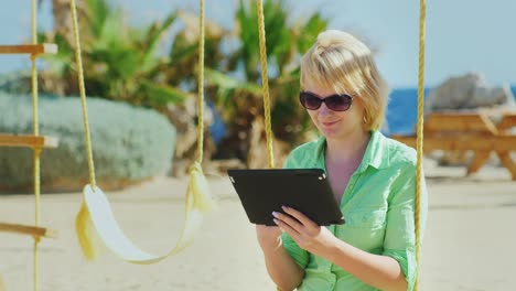 A-Female-Tourist-Enjoys-The-Tablet-Sitting-On-A-Swing