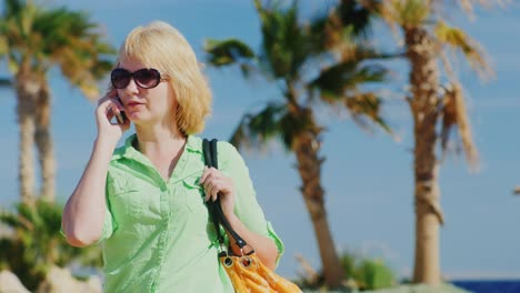 Woman-Tourist-In-Sunglasses-Talking-On-The-Phone-On-The-Background-Of-Sky-And-Palm-Trees