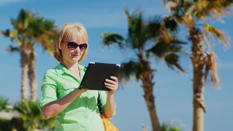 A-Woman-In-A-Light-Green-Shirt-Using-Tablet-Against-The-Sky-And-Palm-Trees