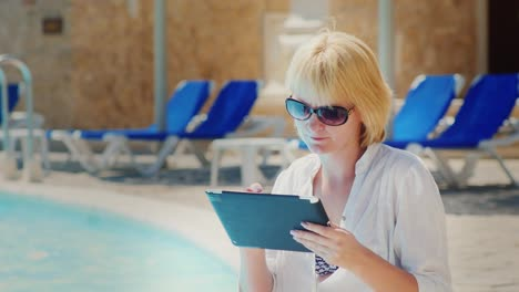 Woman-Relaxing-By-The-Pool-Enjoying-The-Tablet