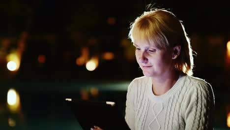 Attractive-Woman-Enjoys-The-Tablet-Late-In-The-Evening-Near-The-Pool