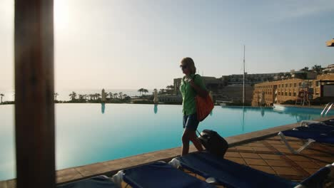 Steadicam-Shot-Of-Woman-With-Travel-Bag-Walking-On-Recreation-Area-Along-The-Pool