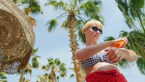 A-Woman-Uses-The-Cream-From-The-Sun-Standing-On-The-Background-Of-Sky-And-Palm-Trees