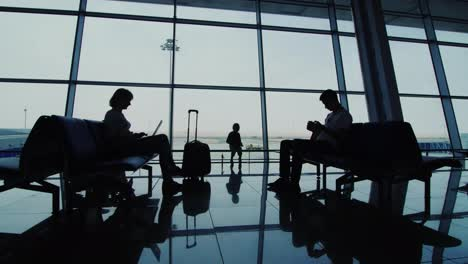 A-Woman-With-A-Child-Awaiting-Her-Flight-Sit-On-Chairs-In-Airport-Terminal-Silhouettes