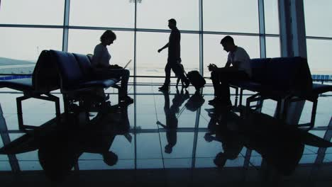 Silhouettes-Of-People-Waiting-For-A-Flight-Use-Gadgets-Walk-With-Hand-Held-Supplies