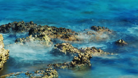 Surf-At-The-Rocks---Red-Stone-On-A-Background-Of-Blue-Sea-4k-Timelapse-Video