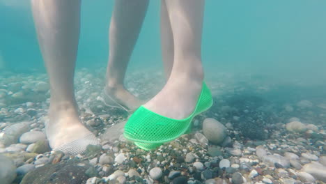 Legs-In-Protective-Shoes-On-The-Pebble-Bottom-Of-The-Sea-Safe-Bathing-In-The-Sea-Concept