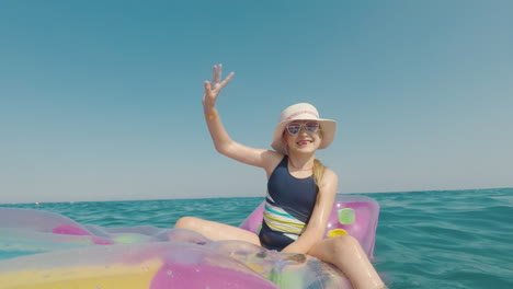 A-Girl-In-A-Hat-And-Sunglasses-Floats-In-The-Sea-On-An-Inflatable-Mattress-Merry-Vacation-Concept