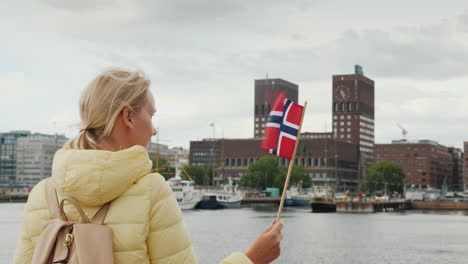 A-Female-Tourist-With-A-Flag-Of-Norway-Is-Standing-On-The-Pier-Looking-Forward-To-The-City-Of-Oslo-T