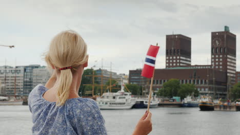 A-Young-Woman-With-A-Norwegian-Flag-Photographes-Herself-Against-The-Background-Of-The-Oslo-City-Lin