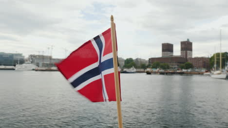 Walking-With-The-Flag-Of-Norway-Against-The-Background-Of-The-City-Line-Of-Oslo-Steadicam-Shot