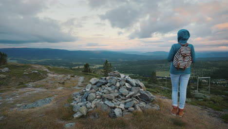 A-Woman-Is-Standing-At-A-Pile-Of-Stones-On-A-Mountain-In-The-Background-Of-A-Dramatic-Sky-A-Rear-Vie