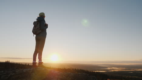 A-Woman-Traveler-Stands-On-Top-Of-A-Mountain-Looks-At-The-Beautiful-Landscape-Ahead-Admires-The-Natu