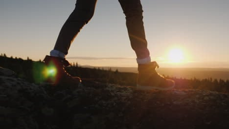 Legs-In-Trekking-Boots-Go-Along-The-Mountain-Ridge-Against-The-Backdrop-Of-The-Rising-Sun-Travel-And