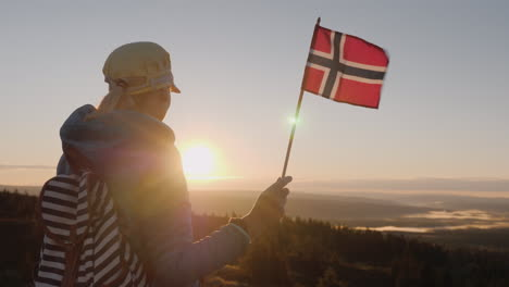 A-Traveler-With-The-Flag-Of-Norway-In-His-Hand-Meets-The-Sunrise-On-The-Top-Of-The-Mountain-Enjoys-T