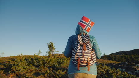 A-Tourist-With-A-Norwegian-Flag-In-A-Backpack-Walks-Through-The-Picturesque-Highlands-At-Dawn-Active